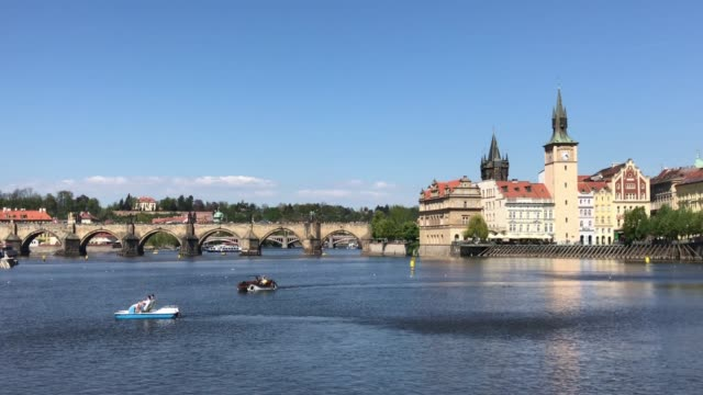 prague vltava river with charles bridge and leisure boats - prague stock videos & royalty-free footage