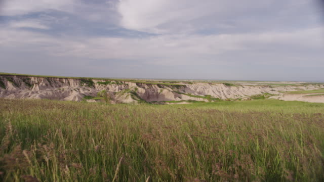 vidéos et rushes de prairie grass blows gently in the foreground of a vast high plains sand hills vista. - grandes plaines américaines