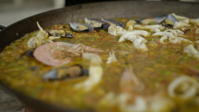 vídeos de stock e filmes b-roll de prawns/shrimp are added to a simmering paella dish - marisco