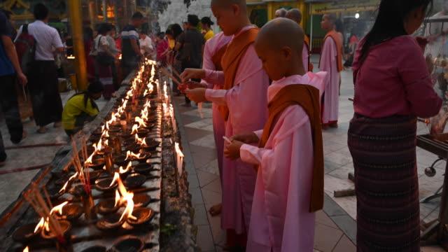 vidéos et rushes de prayer and offerings in the shwedagon pagoda, yangon, myanmar - bougie