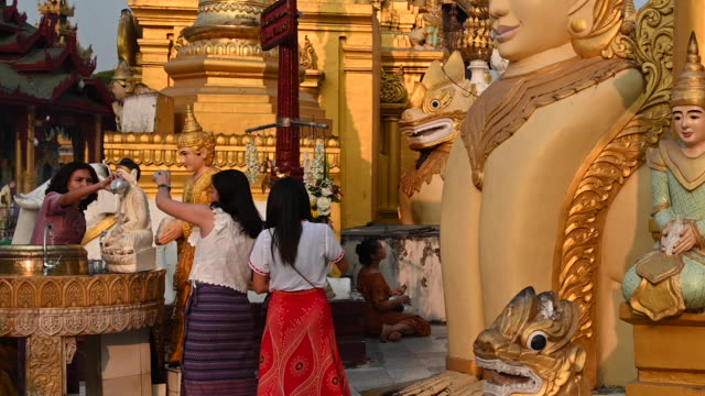 prayer and offerings in the shwedagon pagoda, yangon, myanmar - pagoda点の映像素材/bロール