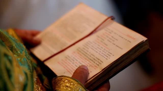 gebetbuch in den händen des priesters - kreuzbein stock-videos und b-roll-filmmaterial