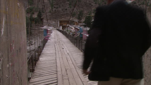 prayer flags flutter on a footbridge. - wood material stock videos & royalty-free footage