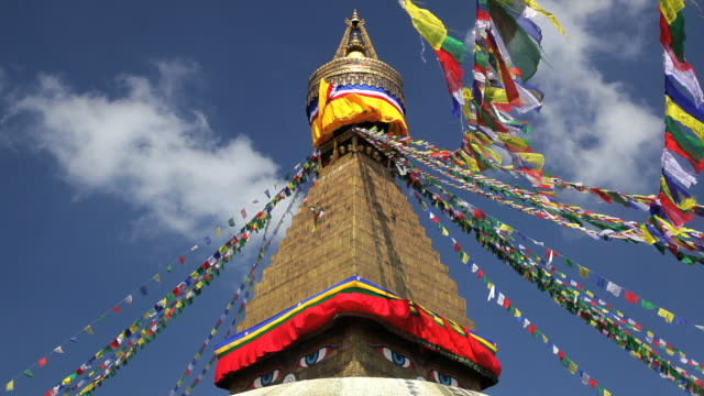 prayer flags flying from the  boudhanath stupa, a place of holy worship, kathmandu, nepal, asia - place of worship stock videos & royalty-free footage