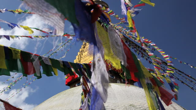 prayer flags flying from the  boudhanath stupa, a place of holy worship, kathmandu, nepal, asia - stupa stock videos & royalty-free footage