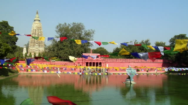 ws prayer flags hanging and blowing in wind above pond at mahabodhi temple / bodh gaya, bihar, india - unknown gender stock videos & royalty-free footage