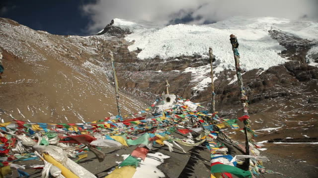 prayer flags under backdrop of snow and darkening sky - traditionally tibetan stock videos & royalty-free footage