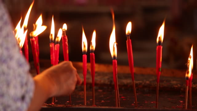 stockvideo's en b-roll-footage met prayer put burning candle into a tray - gelovige
