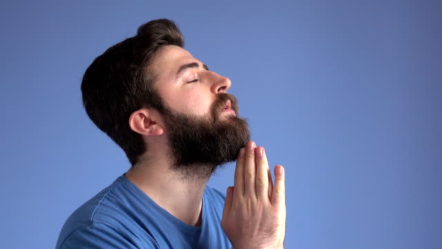 Praying And Contemplating Adult Man On Blue Background