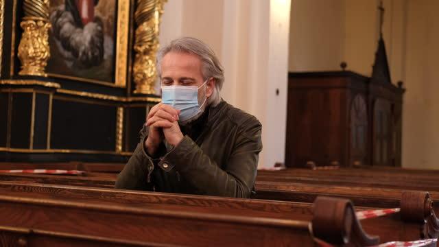 vídeos de stock e filmes b-roll de praying in church wearing mask - religião