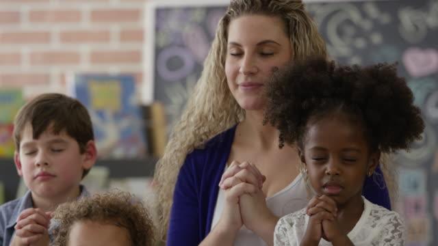stockvideo's en b-roll-footage met bidden in de zondagsschool - peuterschool gebouw