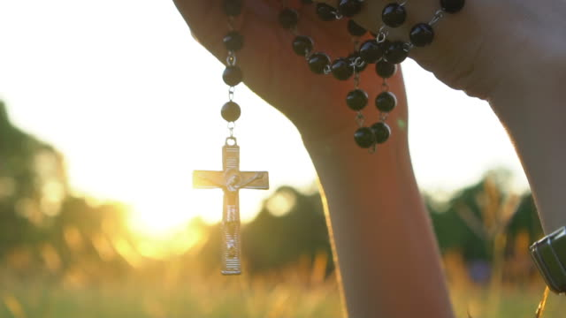 praying with rosary cross - catholicism stock videos & royalty-free footage