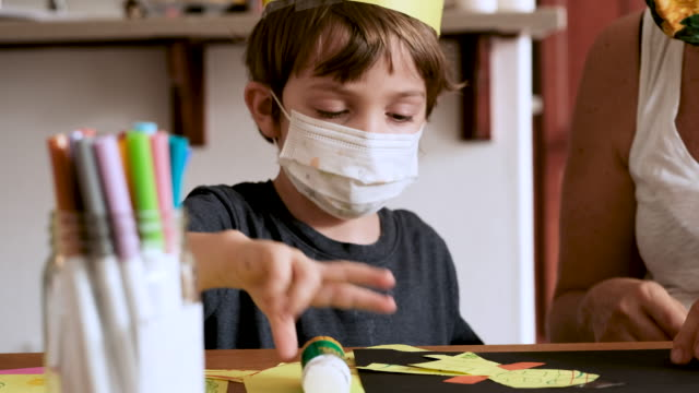 pre school little boy sitting drawing near his teacher wearing a protective face mask - human face drawing stock videos & royalty-free footage