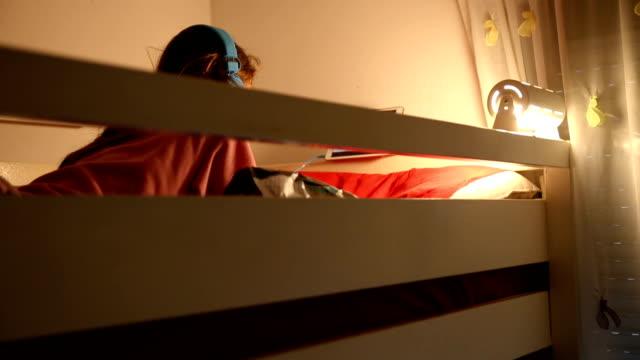 vídeos de stock e filmes b-roll de pre teen girl listening to music or watching a video on her bed - lâmpada elétrica