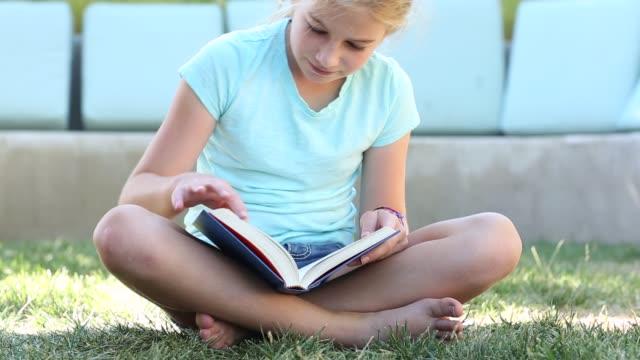 pre teen girl reading - girl sitting cross legged stock videos & royalty-free footage