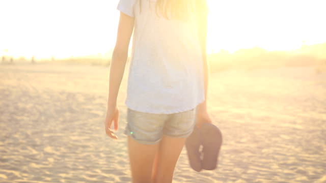 pre teen girl walking on the sand at the beach. beautiful natural sun flare. - flip flop stock videos and b-roll footage