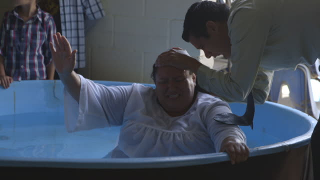 preacher baptizes woman in tub in tijuana - cristianesimo video stock e b–roll