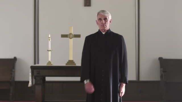preacher checking his watch at the front of a church. - priest stock videos and b-roll footage