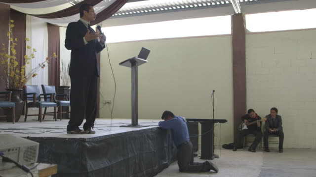 preacher leads prayer in church, wide shot - messen stock-videos und b-roll-filmmaterial