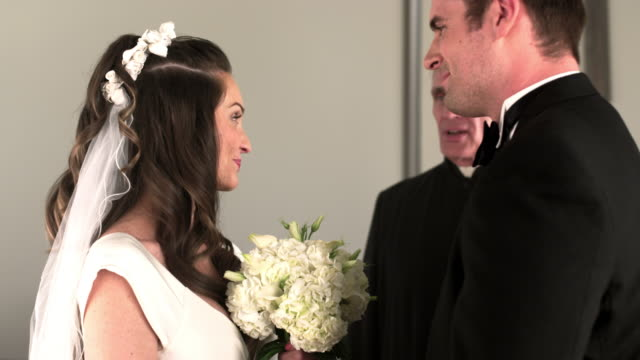 preacher reading to a bride and groom in a church. - preacher stock videos and b-roll footage