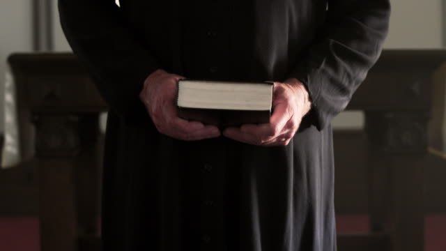 preacher standing, waiting, and holding a book. - clergy stock videos & royalty-free footage
