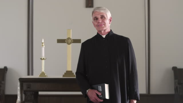 preacher standing with a bible at the front of a chapel. - priest stock videos & royalty-free footage