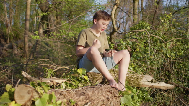 stockvideo's en b-roll-footage met preadolescent 12 years old cute maverick boy gaming outside in green nature with mobile smart phone and winning. - 12 13 jaar