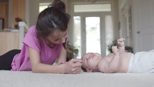 思春期前の女の子は彼女の幼児の妹と遊ぶ - ユーラシアエスニシティ点の映像素材/bロール