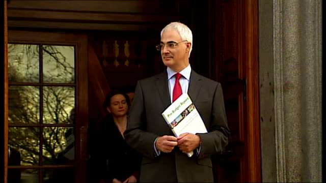 Alistair Darling and team outside Treasury ENGLAND London HM Treasury EXT Alistair Darling MP along through door onto Treasury steps as holding copy...