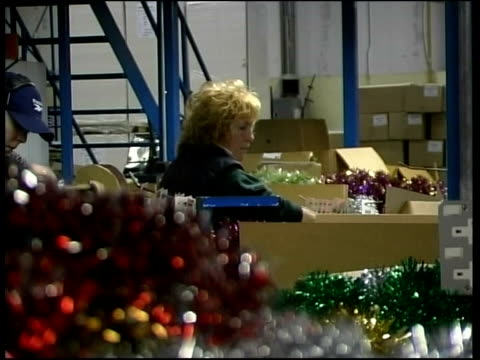 reaction; newcastle: consett christmas company: int man pulling christmas tinsel from manufacturing machine woman packing christmas decorations cms... - tinsel stock videos & royalty-free footage