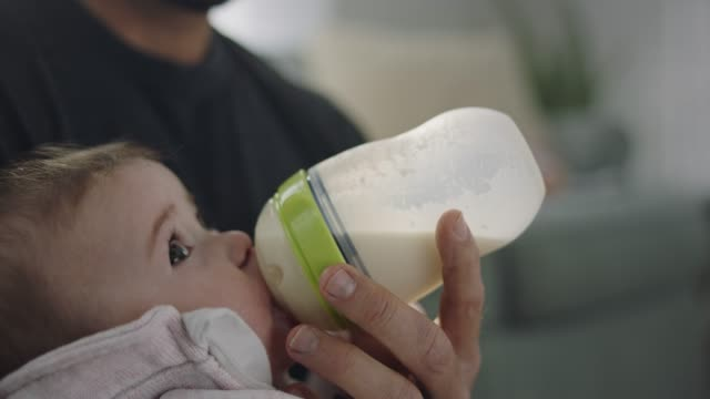 stockvideo's en b-roll-footage met cu slo mo. precious infant daughter drinks milk from baby bottle while cradled in father's arms. - zuigfles