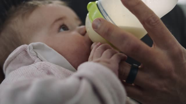 stockvideo's en b-roll-footage met cu slo mo. precious infant daughter wraps tiny hand around dad's finger as she drinks milk from baby bottle. - voeren