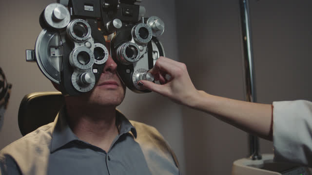 MS. Precise eye doctor switches lenses and adjusts phoropter to determine exact eyeglass prescription for patient.