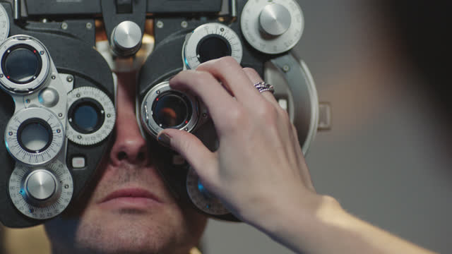 vidéos et rushes de cu ots. precise optometrist switches lenses and adjusts phoropter during routine eye exam. - opticien