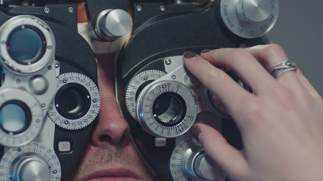 ecu. precise optometrist switches lenses and adjusts phoropter during eye exam. - ehering stock-videos und b-roll-filmmaterial