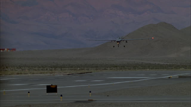 a predator drone comes in for a landing and takes off again before it touches down on the runway. - military stock-videos und b-roll-filmmaterial