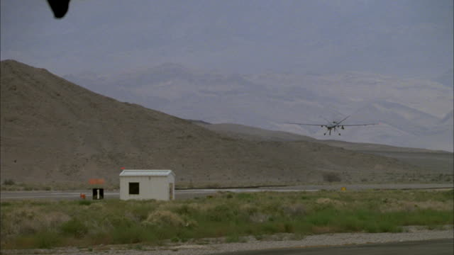 a predator drone comes in for a landing at a rural airport. - heer stock-videos und b-roll-filmmaterial