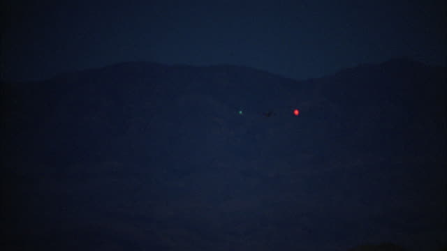 a predator drone lands on a runway in a valley. - heer stock-videos und b-roll-filmmaterial