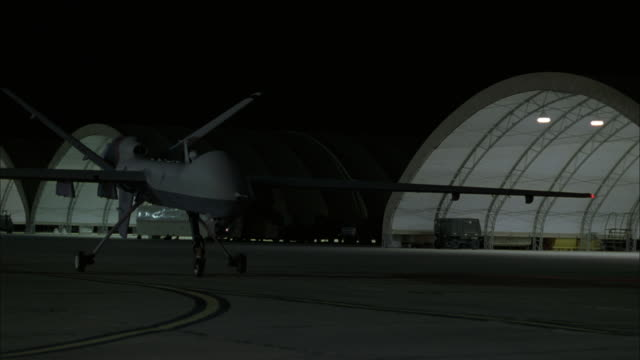 a predator drone taxis away from a large aircraft hangar. - airplane hangar stock videos & royalty-free footage