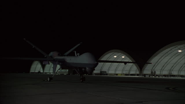 a predator drone taxis on a runway near several hangars at night. - 無人航空機点の映像素材/bロール