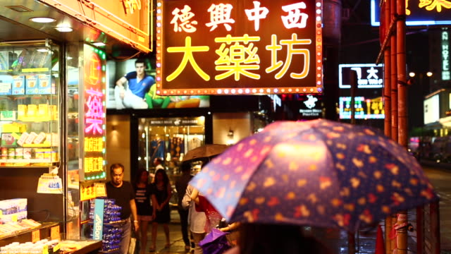 stockvideo's en b-roll-footage met predestrians walking at night in rainy hong kong - hong kong
