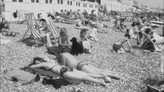 stockvideo's en b-roll-footage met predicted long dry summer could lead to hosepipe ban fs130776008 / eastbourne b/w girl blowing up rubber ring b/w various of people sunbathing on... - rubber ring