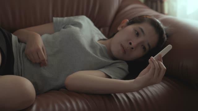 Schwangerschaftskonzept, Asian Woman mit einem Schwangerschaftstest positives Ergebnis auf Sofa zu Hause
