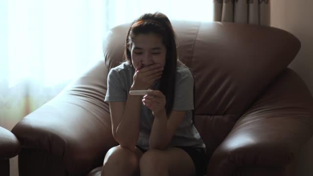 vídeos de stock, filmes e b-roll de conceito da gravidez, mulher asiática com um teste de gravidez resultado positivo no sofá em casa - discovery