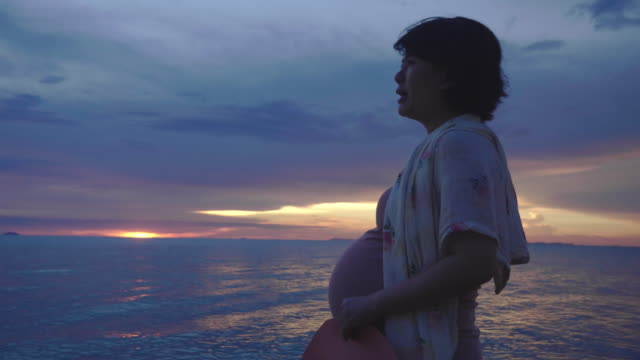 pregnancy relaxation on the beach. - maternity wear stock videos & royalty-free footage
