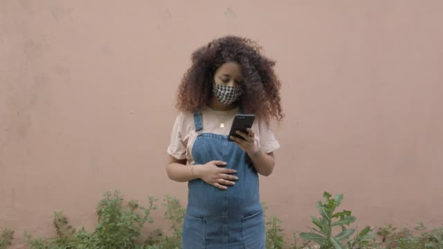 pregnant afro hair woman in the city wearing a cloth protective mask - pregnant stock videos & royalty-free footage