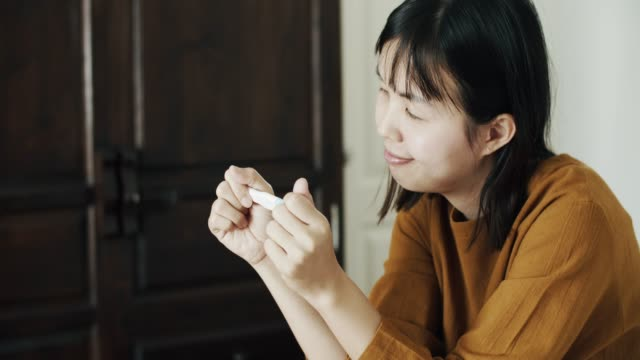 pregnant asian woman holding positive pregnancy test in bedroom - ovulazione video stock e b–roll