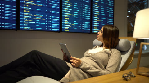 pregnant business woman relaxing at the airport's vip lounge using tablet and looking at the flight schedule - gate stock videos & royalty-free footage
