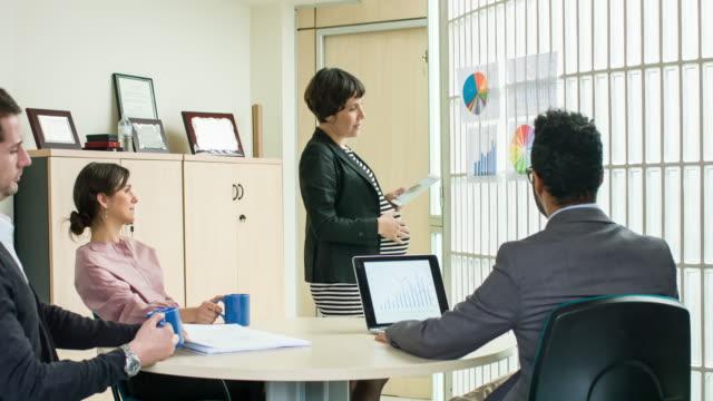 Pregnant businesswoman analysing their company