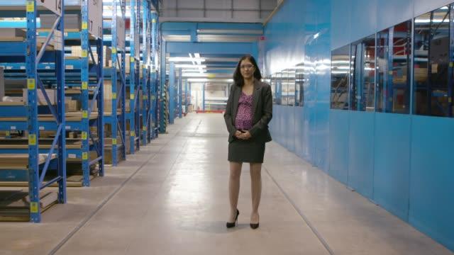 vídeos de stock e filmes b-roll de pregnant businesswoman standing in a warehouse - de corpo inteiro